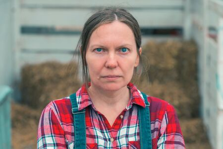 Serious concerned female farmer posing on farm. Confident woman farm worker wearing plaid shirt and jeans overalls looking at camera.