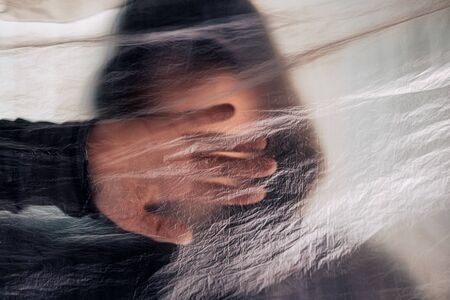 Drug addiction concept, blurred male person with hoodie behind plastic curtain, selective focus Stock Photo