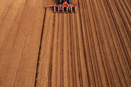 Drone photography of tractor with seeder working in field, agricultural machinery is planting seed into freshly plowed land