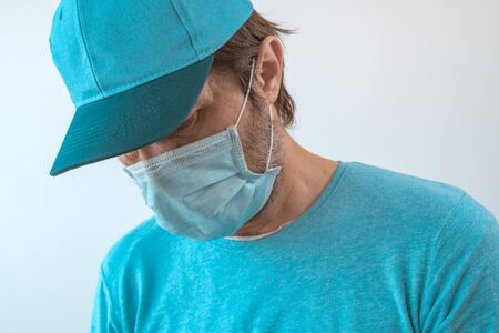 Delivery guy with face protective mask during virus outbreak lockdown wearing blue t-shirt and baseball cap, selective focus