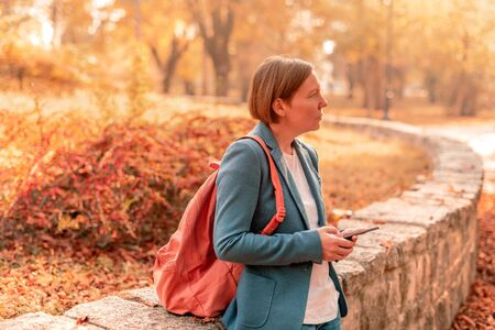 Businesswoman using mobile phone in autumn park, typing text message or e-mail reply, selective focus Banque d'images