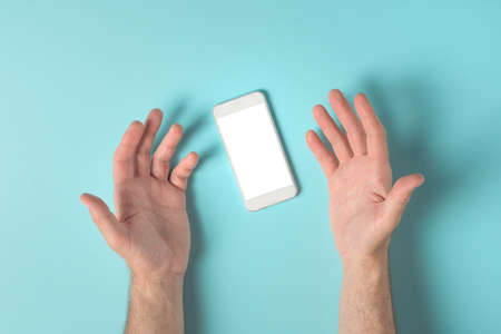 Frustrated male hands over smartphone screen mock up copy space, top view
