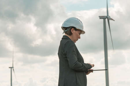 Female engineer with tablet computer on modern wind turbine farm during maintenance project planning