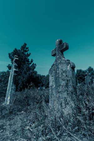 Old cross headstone on the graveyard, spooky atmospheric image