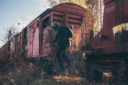 Homeless immigrant with hoodie jumping off old train wagons, selective focus Stock Photo