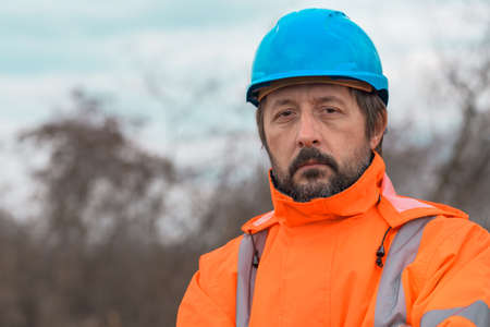 Portrait of confident forestry technician in woodland. Adult professional male wearing hi-viz blaze orange jacket and blue hardhat. Stock fotó
