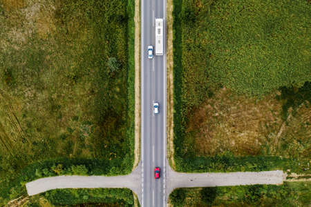 Aerial view of three cars and passenger bus on the road, top view from drone pov