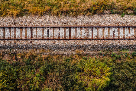 Old railroad track through countryside in autumn, aerial view from drone pov Banque d'images
