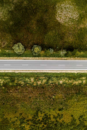 Empty asphalt road through countryside, aerial view from drone pov
