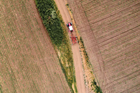 Aerial view of agricultural tractor on dirt road driving through cultivated fields, drone pov Banque d'images