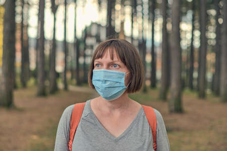 Casual woman in everyday protective face mask concept posing in park, wearing surgical mask as new normal routine accessory