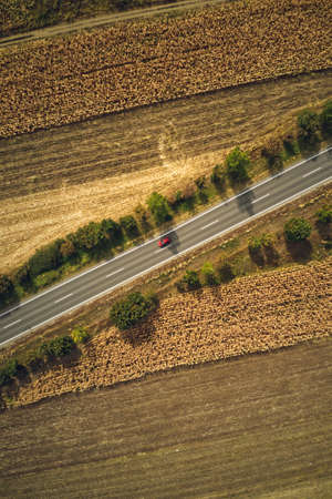 Single red car on the road, top view from drone pov. Aerial photography of vehicle on roadway through countryside in summer.