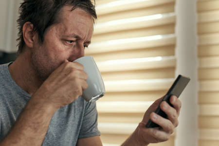 Man drinking coffee and using mobile phone at home, adult caucasian male enjoying morning routine