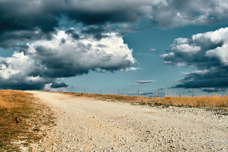 Empty pebble road to nowhere disappearing on the horizon with blue sky and dramatic clouds
