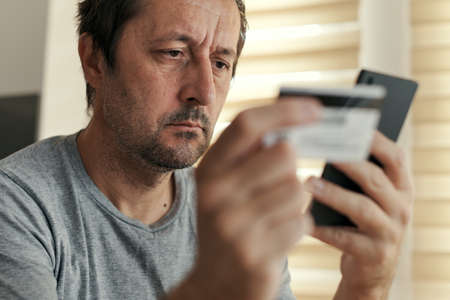 Man shopping online from home with mobile phone and credit card, adult male buying on internet from his living room