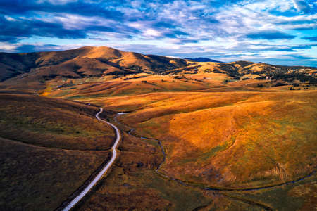 Aerial view of beautiful Zlatibor region landscape with asphalt road passing through from drone pov. Zlatibor is mountain located in south-west Serbia Banco de Imagens