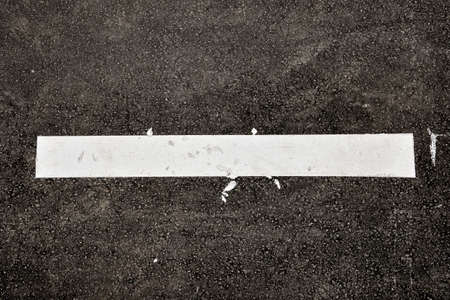 White line on black asphalt road, top view