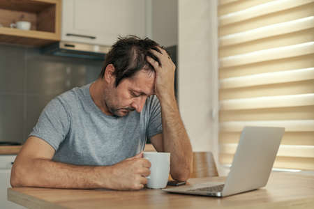 Disappointed freelancer at home office having job problems with his head in hands, selective focus