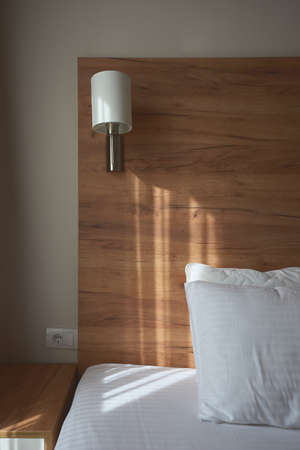 Apartment bedside for travel and tourism concept, sunlight falling from curtains on bed and pillows Banque d'images