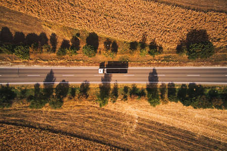 Top view aerial photo of truck on the road through plain landscape countryside in summer afternoon Banque d'images