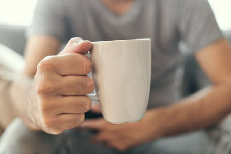 Man holding coffee cup in living room, close up of hands with white mug, selective focus Banque d'images