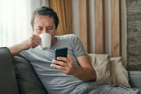 Man drinking coffee and using mobile phone at home, adult caucasian male enjoying morning routine at living room sofa