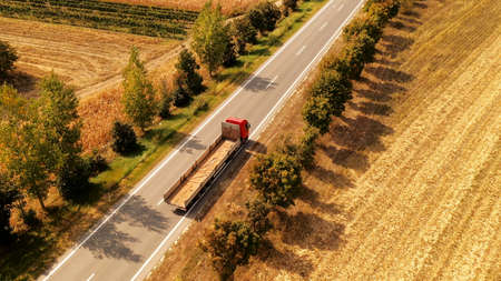Truck on the road through countryside, aerial view of freight transporter driving through rural landscape in summer