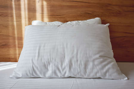 White pillow on bed in apartment bedroom with morning sunlight beaming through curtains