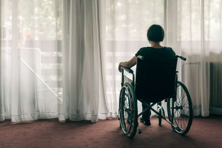Depressed sad woman in worn wheelchair looking out the window and thinking, lonely disabled adult caucasian person indoors Banque d'images