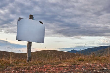 Blank signpost mock up in front of beautiful mountain landscape scenery at sunrise