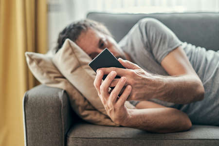 Depressed man using mobile phone while lying at living room sofa, adult sad lonely male sulking at home Banque d'images