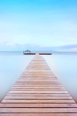 Träbrygga i en kall miljö En lång exponering fotografi taget i höst i en strand med toskanska kusten