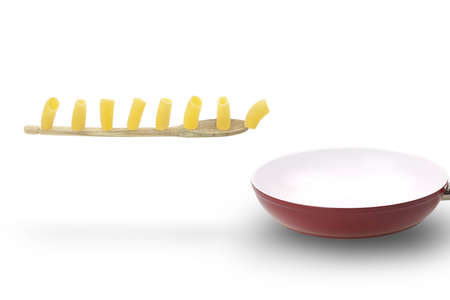 Paccheri, a typical italian pasta, march on wooden spoon into a ceramic pan. photo