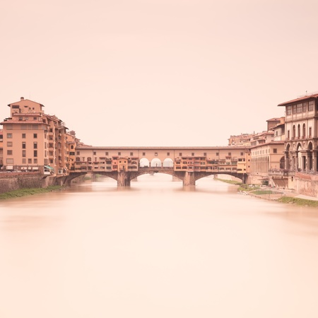 florence: Ponte Vecchio medieval landmark on Arno river in a warm vintage mood taken through a 2 minute long exposure photography in a light foggy day  Florence, Tuscany, Italy  Stock Photo