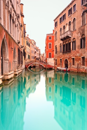Water Canal and Bridge in Venice in a long exposure photography. Venetian buildings in its typical architecture and a boat on right side. Stock Photo