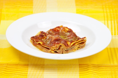 Lasagna alla bolognese traditional italian recipe with meat, tomato, parmigiano cheese, olive oil, lasagne pasta on a round plate on colorful tablecloth. photo
