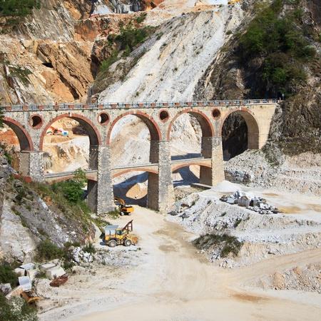 carrara: White marble quarry old bridge and excavators at work  Apuan Alps, Carrara, Tuscany, Italy, Europe
