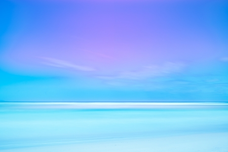 Long exposure photography with soft sea and light cloudy blue sky  2 minutes time exposure on a white beach