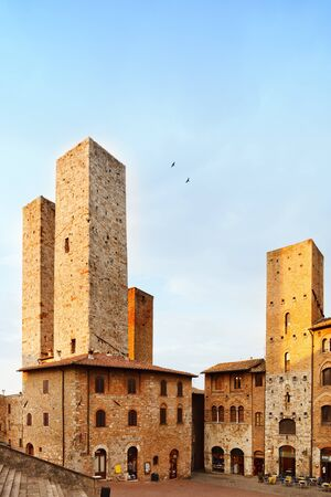 San Gimignano landmark medieval town  Sunset on towers in central Erbe Square  Tuscany, Italy, Europe  photo