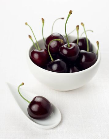 dark cherry: Single cherry on a white china spoon and a ripe group cherries in a small round white bowl
