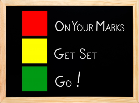 On Your Mark, Get Set, Go written on blackboard or chalkboard with traffic light red yellow green colors  photo