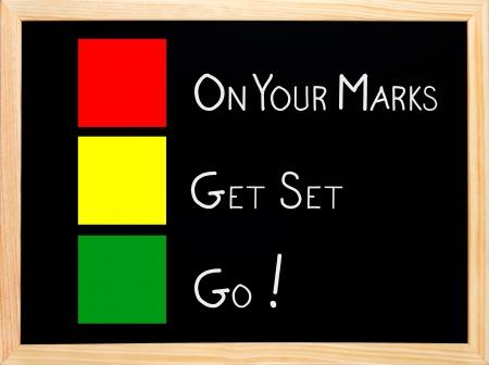 På Din Mark, färdiga, gå skriven på tavlan eller tavlan med trafikljus röd gul gröna färger Stockfoto