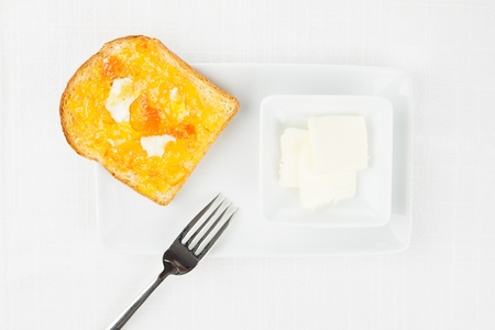 French toast with spread bitter orange marmalade or jam with candied peel, butter curls, fork and dishware on white tablecloth photo