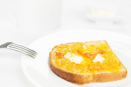 marmalade: Breakfast  French toast with spread bitter orange marmalade or jam with candied peel, butter curls, fork on background and a cup and dishware on white tablecloth