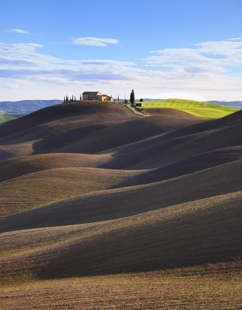 Tuscany, rural landscape in Crete Sensi land  Plowed rolling hills, countryside farm, cypresses trees, green field and blue sky  Siena, Italy, Europe  photo