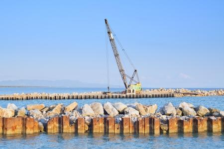Crawler Crane at work on rocks harbor near river and sea shore  photo