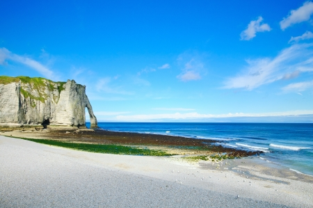 Etretat Aval cliff landmark and its beach and a blue sky. Normandy, France, Europe. photo