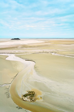 Low tide and rock formations in Mont Saint Michel Bay landmark  Normandy, France, Europe photo