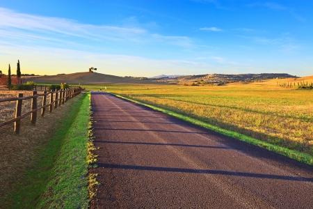 Toscana, Maremma typiska landsbygden solnedgång landskap med landsbygdens väg, staket, gröna fält, träd, lantlig torn och byn på bakgrund Italien, Europa