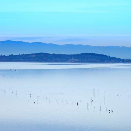 redes de pesca: Las redes de pesca y un p�jaro en un paisaje tranquilo azul del Lago Trasimeno en la puesta del sol Umbr�a, Italia